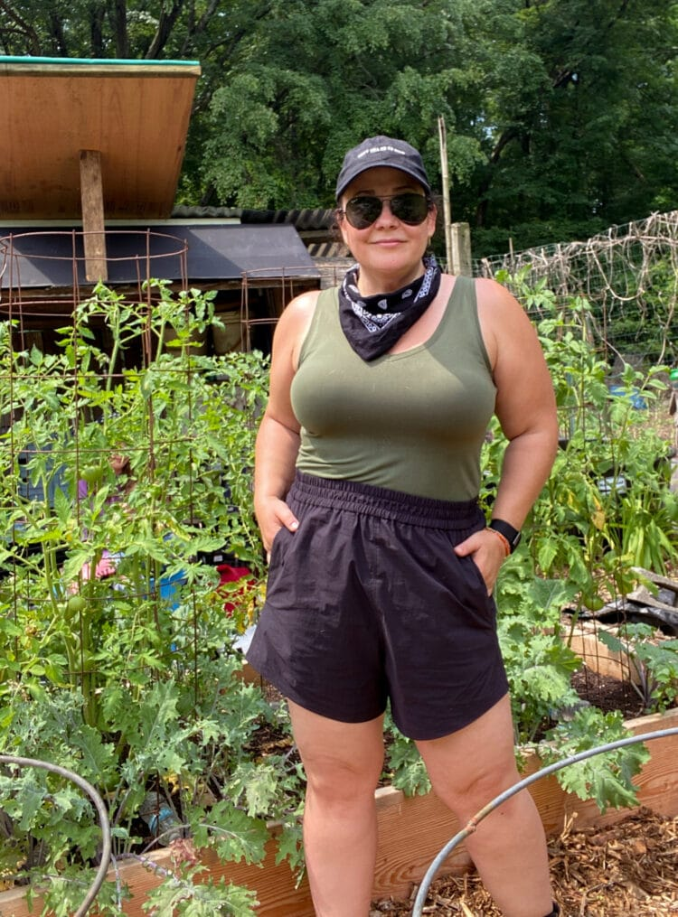 IMO the best size-inclusive active shorts are the Universal Standard Sunny Swim Shorts which I am wearing here in black with an olive fitted tank while working in my garden.