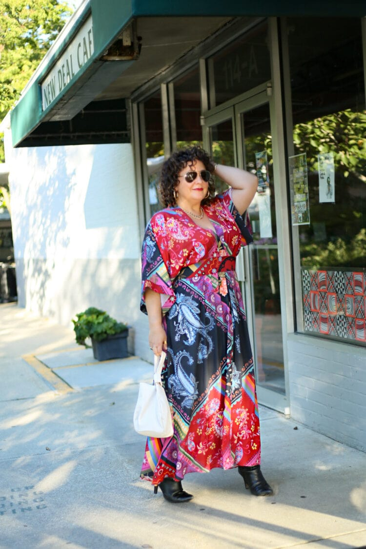 Wardrobe Oxygen standing outside the New Deal Cafe wearing a red printed maxi dress carrying an ivory bag