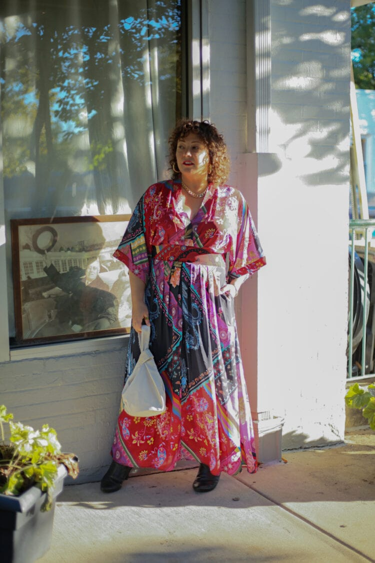 Wardrobe Oxygen in a printed maxi dress against a white brick wall wearing Ros Hommerson Maryland wide calf boots