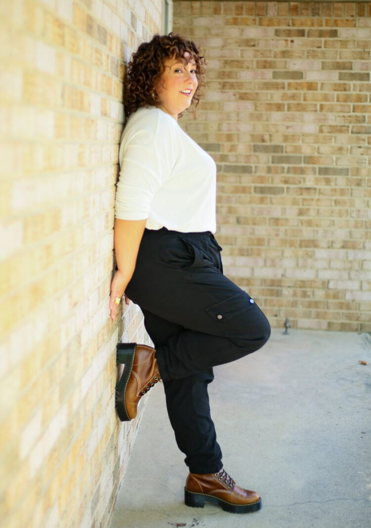 Alison of Wardrobe Oxygen leaning against a brick wall with one foot up showing her brown Doc Marten boots