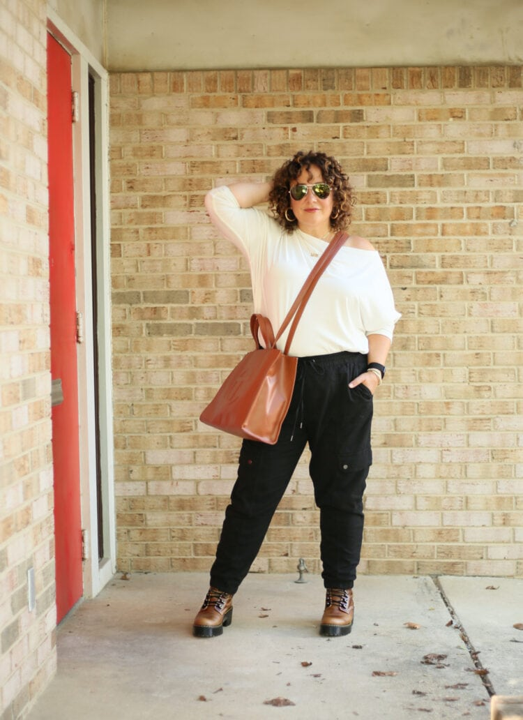 Wardrobe Oxygen in a white ALLSAINTS off the shoulder long sleeved top with black jogger inspired black cargo pants from Banana Republic and a tan TELFAR medium tote worn as a crossbody. She is standing in front of a brick wall wearing sunglasses and facing the camera, one hand in her hair.