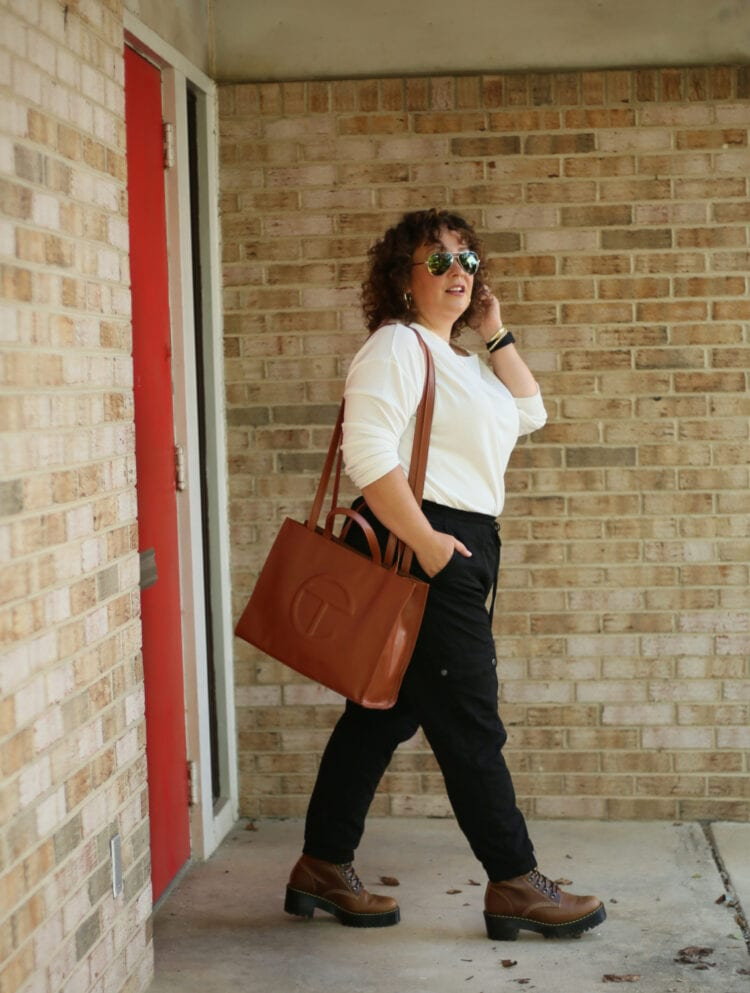 Alison of Wardrobe Oxygen wearing a medium TELFAR bag over her shoulder as she walks out from a brick building